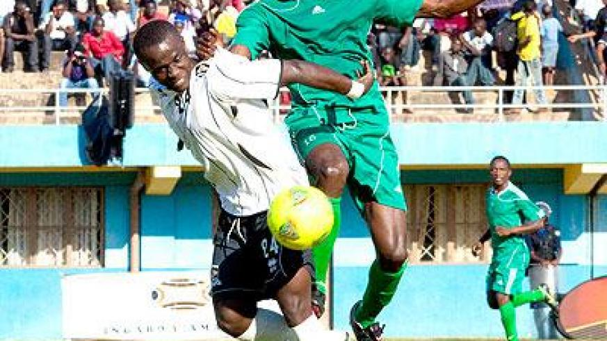 Striker Michel Ndahinduka shields the ball from Kiyovu defender. He netted the winning goal in the 79th minute to send APR on top of the national football league table. Sunday Spor....