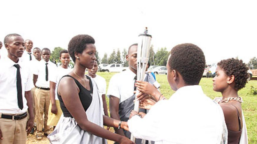 <p>Students of Nyange school in Ngororero receive the Kwibuka Flame on January 10 as the torch embarked on its nationwide lap of honour ahead of the 20th anniversary of the 1994 Genocide against the Tutsi. Nyange school (in the background, right) was on March 18, 1997 attacked by the remnants of the Genocide machinery, with the assailants killing six students after the youngsters refused to separate themselves along ethnic lines. Both the victims and the survivors of the attack are among the heroes  feted today. The New Times/T. Kisambira.</p>