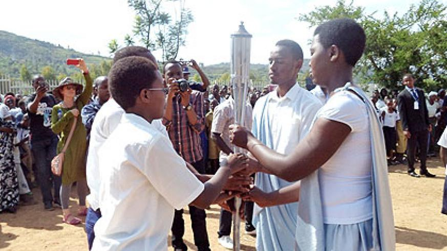 Students from Nyaruguru (L) hand over the Flame to those from Nyamagabe as the iconic torch of remembrance marked its ninth stop of the national tour. The New Times/ JP Bucyensenge.