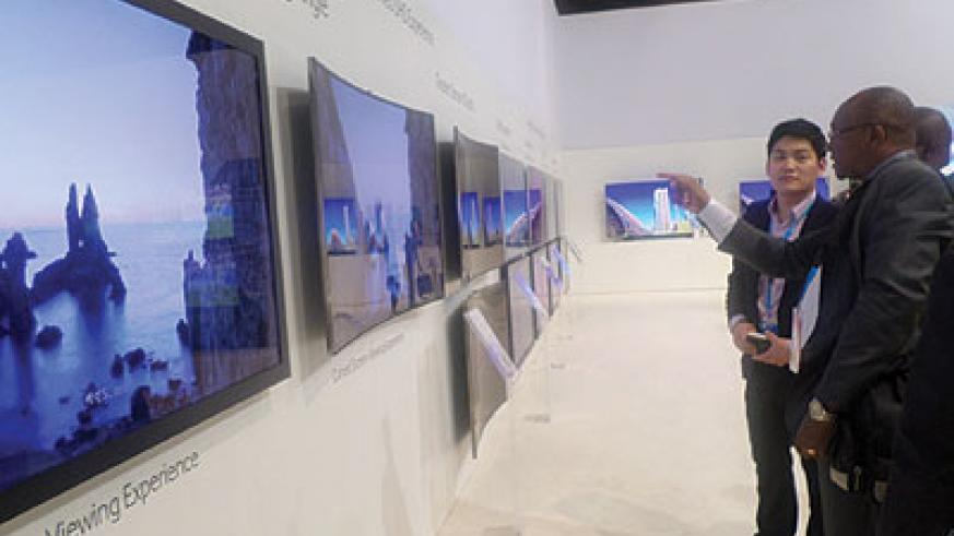 COMPARISON: A journalist (right) reacts after noticing the big picture quality difference between a flat TV set (left) and curved TVs. The New Times / Stephen Nuwagira