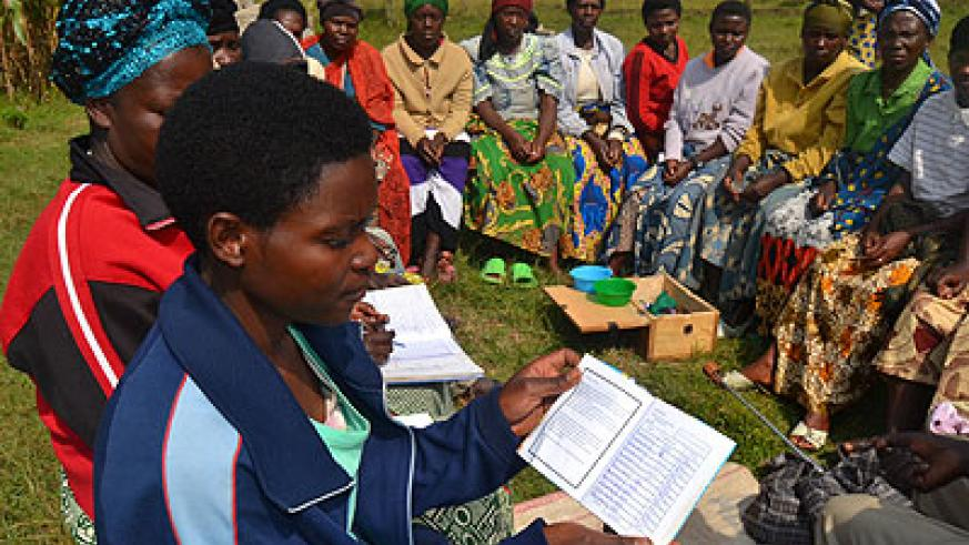 A woman shows how they record their money they save in individual booklets. Jean d'Amour Mbonyinshuti.