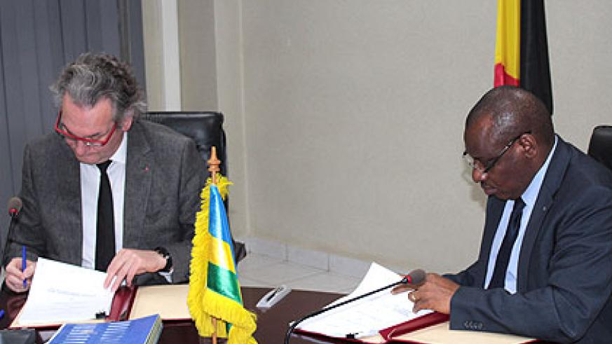 Jean-Pascal Labille and Claver Gatete sign the agreement. Courtesy