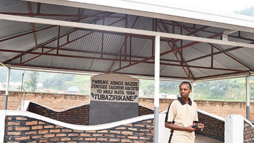 Innocent Kabanda stands next to the memorial site established in memory of thousands of Tutsis who were slain  and buried in the pit .  Jean d'Amour Mbonyinshuti .