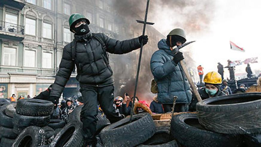 Protesters stand on a barricade during an anti-government protest in downtown Kiev. Net photo.