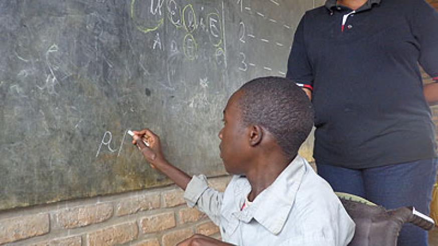 Imanizabayo illustrates something on the blackboard as his teacher pays close attention. /Jean Tabaro