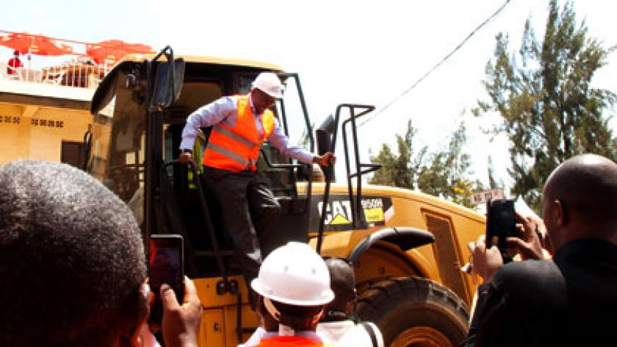 Minister Musoni alights from an excavator after launching the projects for feeder roads in Kigali yesterday. Timothy Kisambira.
