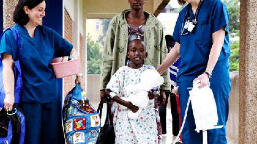 Fidel Mihoza,  one of the children who underwent free open heart surgery at King Faisal Hospital last year is sandwiched by his mother Immaculée Mahombi (behind), and some of the ....
