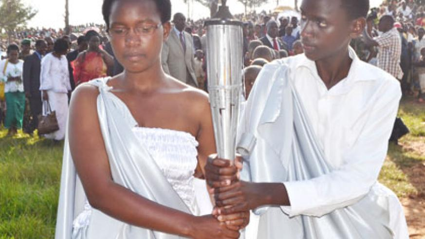 Two youths carry the Kwibuka Flame in Ruli Sector, Gakenke District, where residents were urged to promote unity. Jean d'Amour Mbonyinshuti.