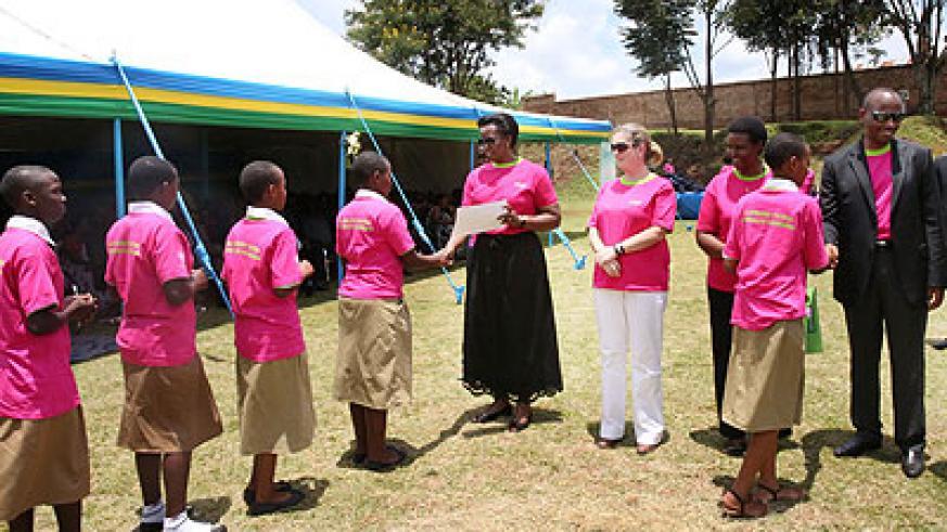 The First Lady, Jeannette Kagame, hands out certificates to some of the best performing school girls. On her immediate left is the Unicef country representative, Noala Skinner. Vil....