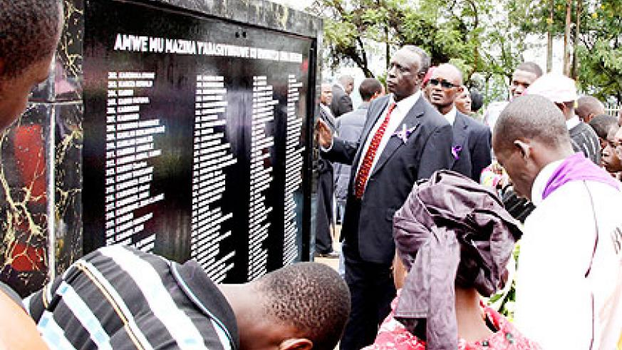Survivors look at a wall in Rebero in Kigali bearing names of their relatives who perished during the Genocide. (File)