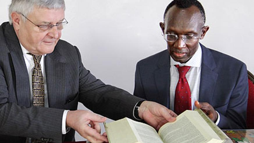 Chief Justice Sam Rugege (R), and former ICTR Judge Wolfgang Schomburg look through a book during the workshop yesterday. (John Mbanda)