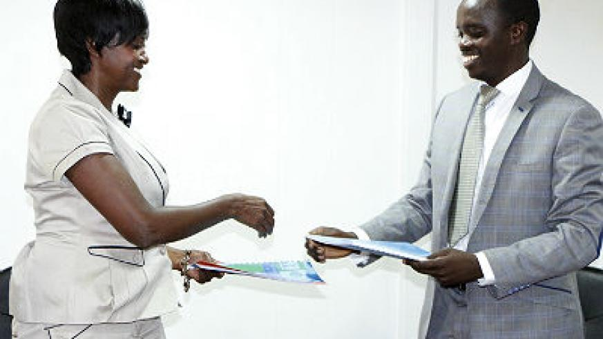 Maria Legodi Busisiwe, Director General, CIMERWA (L), and Pierre Kalinganire, Chief Executive Officer, Peat Energy Company, exchange documents after signing the deal. (Courtesy)