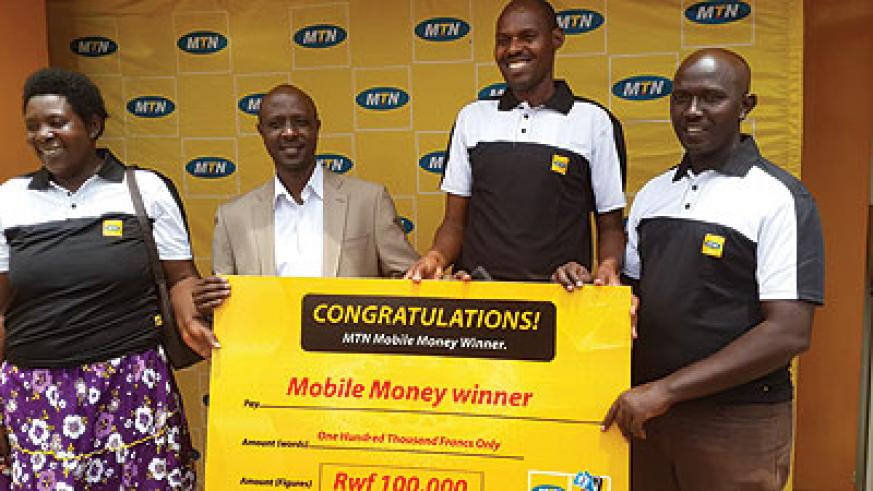 Some of the winners receive a dummy cheque from Munyampundu (second left) at the MTN Service Centre in Kimironko. The New Times/Ben Gasore.