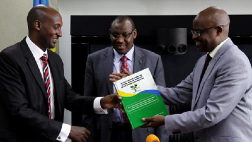 Ben Kagarama (R) gives a book containing Rwanda's fiscal laws and regulations to new RRA boss Richard Tusabe as Minister Gatete looks on during the handover yesterday. John Mbanda.