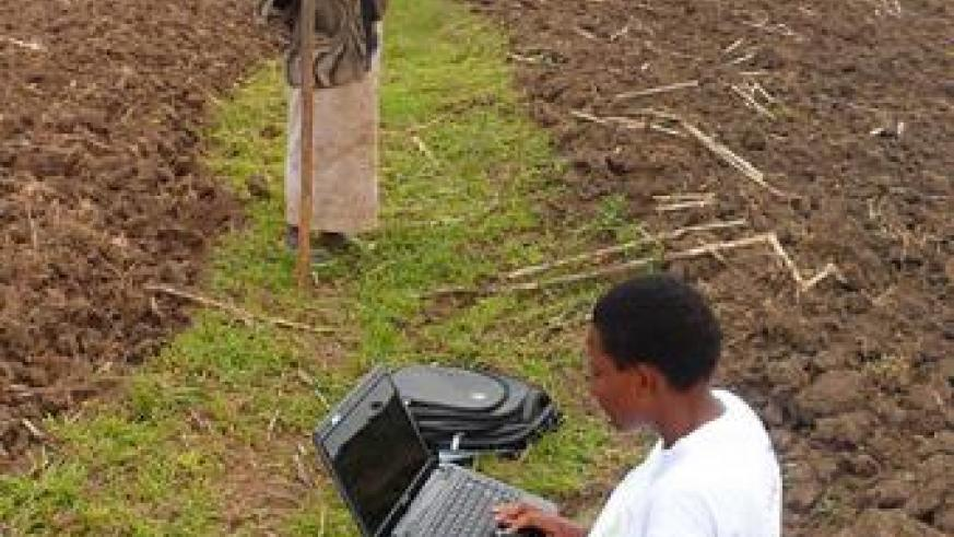 Umutesi uses a laptop to collect data on agriculture. Courtesy photo