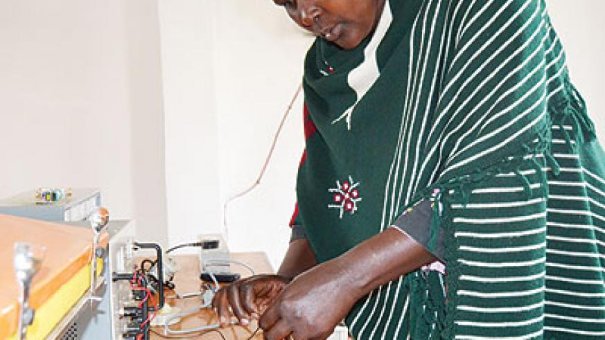 Uzamukunda arranges wires in her office. She is working with other rural women in distributing solar energy. (Jean d'Amour Mbonyinshuti)