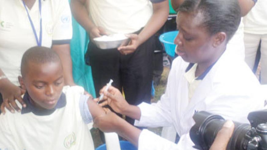 Minister Asiimwe administering a vaccine against cervical cancer during the launch. (Ivan Ngoboka)