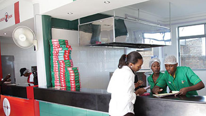 Woodland Pizza Inn workers serve a customer. The firm offers client-centred services at all its businesses.  The New Times / John Mbanda