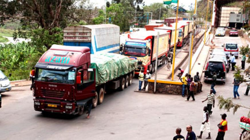 Trucks clear transit goods at Rusumo border post. Traders will in two years be able to use local currencies across EAC borders. File.