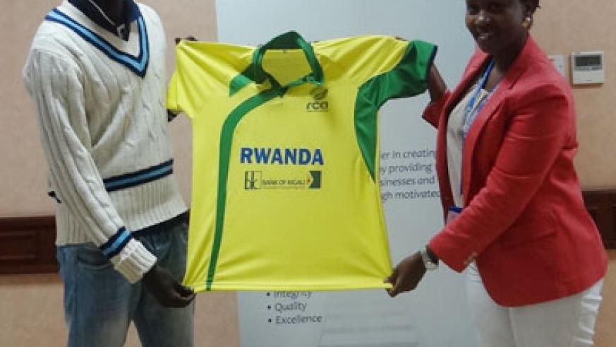 Bank of Kigali's Shivon, right hands over playing attire to national team captain Eric Dusingizimana at the bank's headquarters . Courtesy.