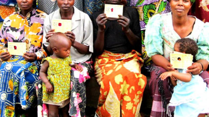 Women pose with their Mutuelle de Sante cards. Private insurance firms have expressed mixed feelings over the government's plan to increase health insurance premium from the curren....