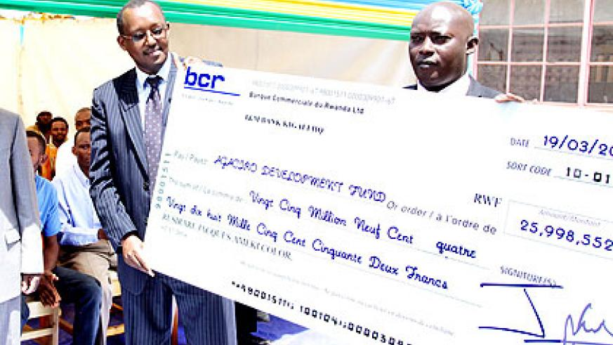 Kagabo and Ndamage hold a dummy cheque from Ameki Color. John