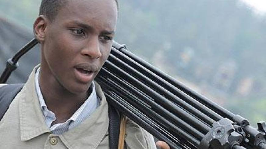 Ishimwe carries his equipment as he prepares to start work. (Moses Opobo)