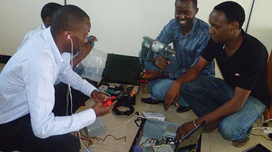 Cyusa (second, left) and his team testing communication speed of a device. Cyusa's firm offers WiFi services among others. The New Times / Seraphine Habimana