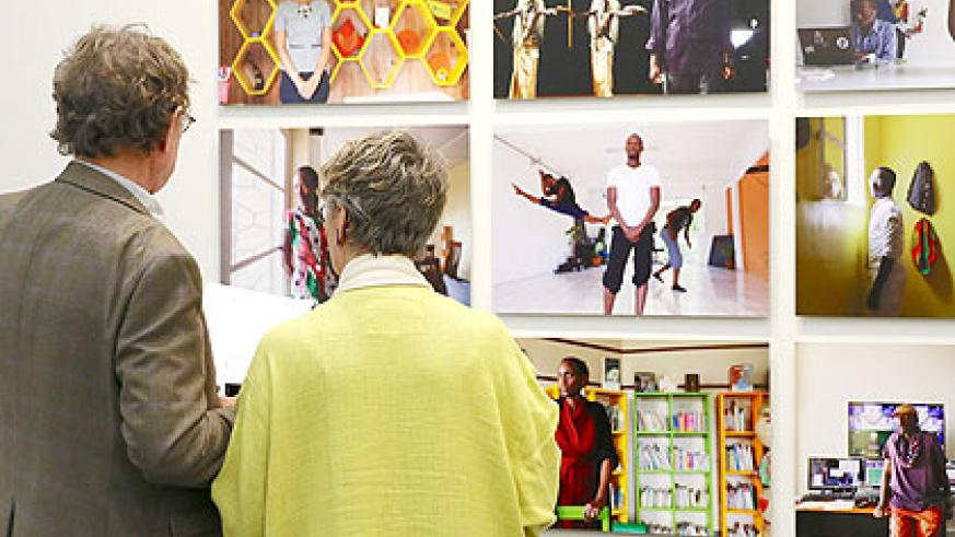 A curator takes a visitor at the exhibition through various pictures depicting lifestyle in Rwanda. (Courtesy)