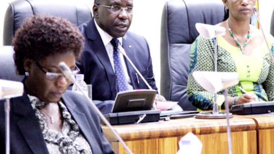 Premier Habumuremyi (C) delivers the economy report in Parliament as State Minister for Local Government Alivera Mukabaramba (L) and Senate Deputy President Jeanne d'Arc Gakuba f....