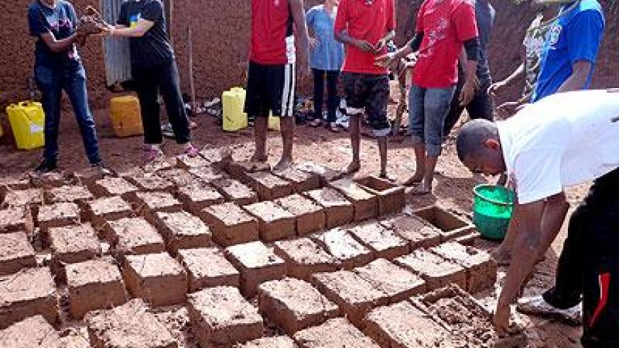 Youth make bricks for Mukarusasa's house. (Jean de la Croix Tabaro)