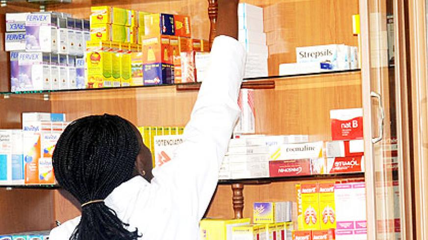 A pharmacist in Kigali picks drugs from the shelf to serve a client. UK's GlaxoSmithKline pharmaceutical firm will enhance quality and access to drugs in the country once it sets....