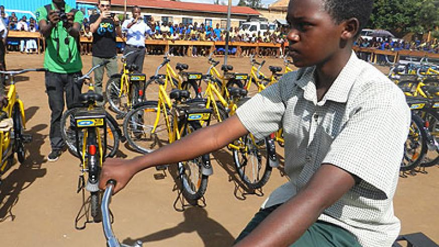 One of the beneficiaries from Nsinda Secondary School takes a ride on her bicycle. (Stephen Rwembeho)