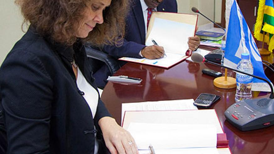 World Bank's Turk (L) and Amb. Gatete sign the feeder roads deal in Kigali yesterday. (Timothy Kisambira)