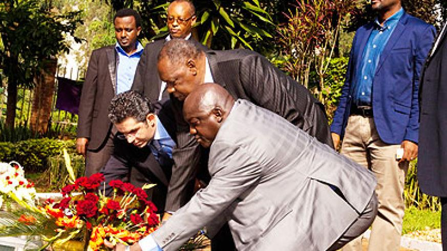 Caf president Issa Hayatou (C), vice president Almamy Kabele Camara (L) and secretary general, Hicham El Amrani (R) lay a wreath in honour of the Genocide victims at the Kigali Mem....