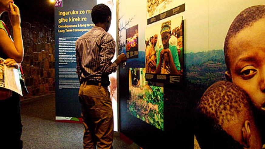Visitors look at wall pictures at Kigali Genocide Memorial Centre in Gisozi depicting the impact of the Genocide. (Timothy Kisambira)