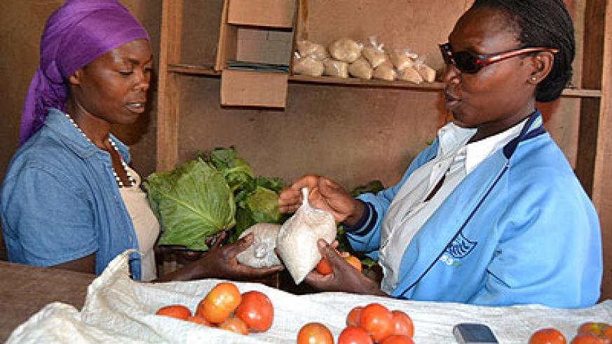 Dunia serves a buyer. She was rejected by her husband after she became visually impaired in 2001.   Jean d'Amour Mbonyinshuti
