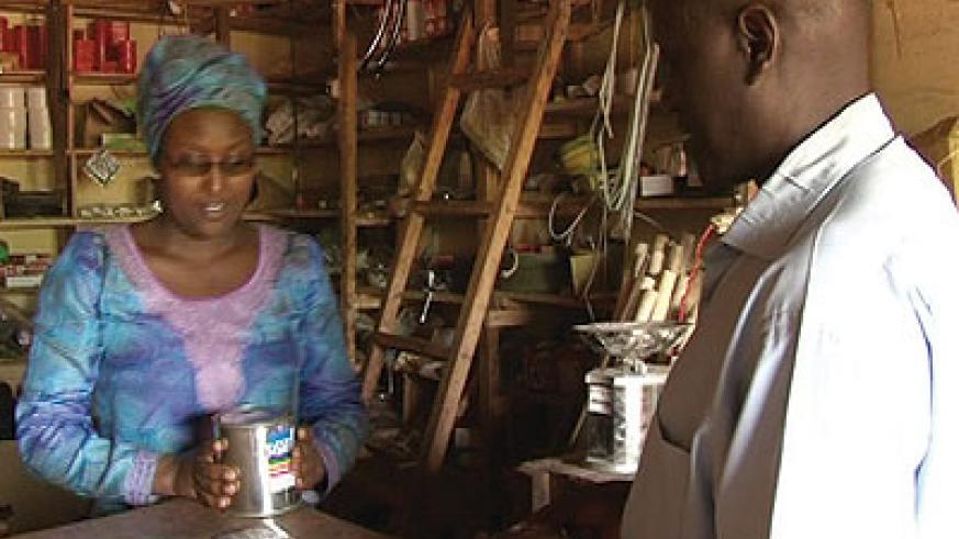 Umurerwa serves a client at her store. The New Times / Seraphine Habimana.