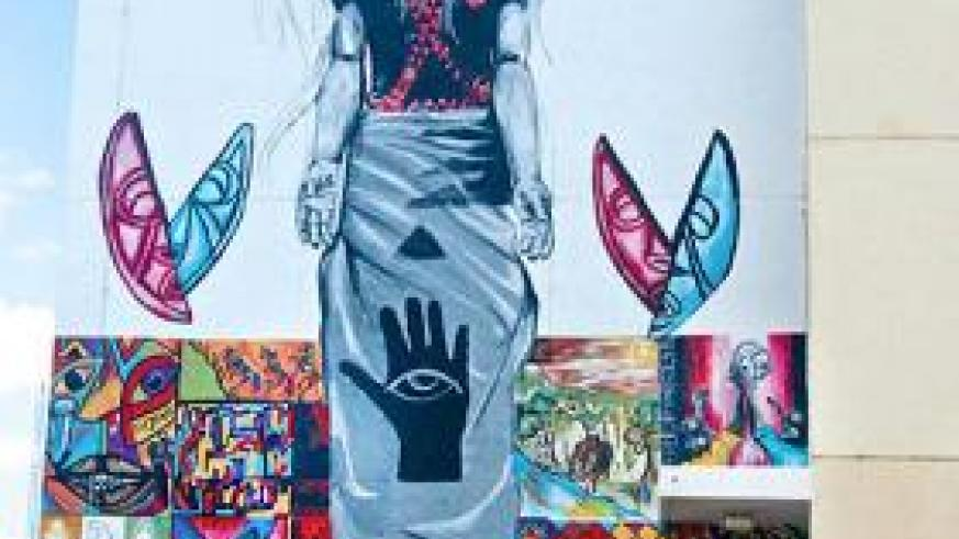 """A tall mural on a wall of the Rwanda Biomedical Center (RBC) building features artworks against HIV stigma and promotes """"positive living"""" within the community."""