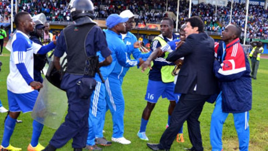 Rayon Sports head coach Luc Eymael and Cedric Amissi seen being restrained from attacking match officials yesterday at Amahoro stadium. S. Ngendahimana.