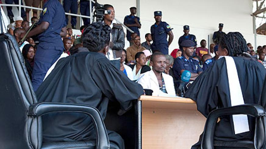 Sylvestre Hora (centre), the convicted murderer of 12-year-old Shalom 'Bella' Uwase, listens as the bench reads out the verdict at Kigali Regional Stadium yesterday.  He was se....