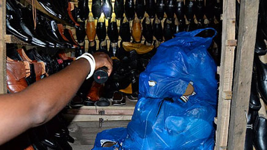 A trader uses her torch to look at her shoes.  Jean Mbonyinshuti