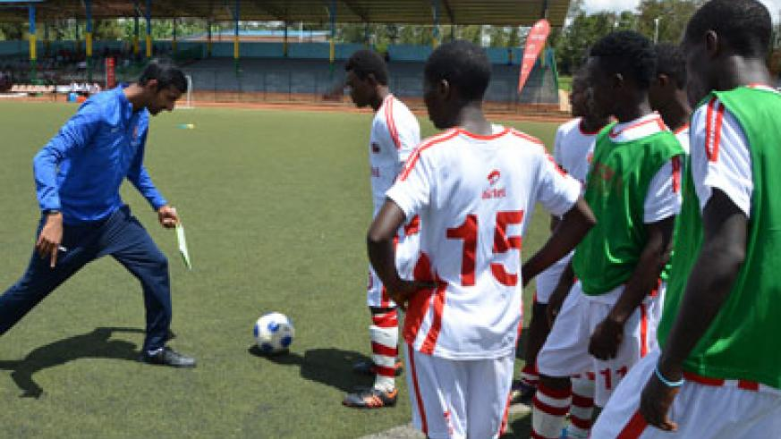 Rupen Shah, left, one of the two coaches from the Arsenal Academy School, taking the youth players through the first session yesterday. Sam Ngendahimana.