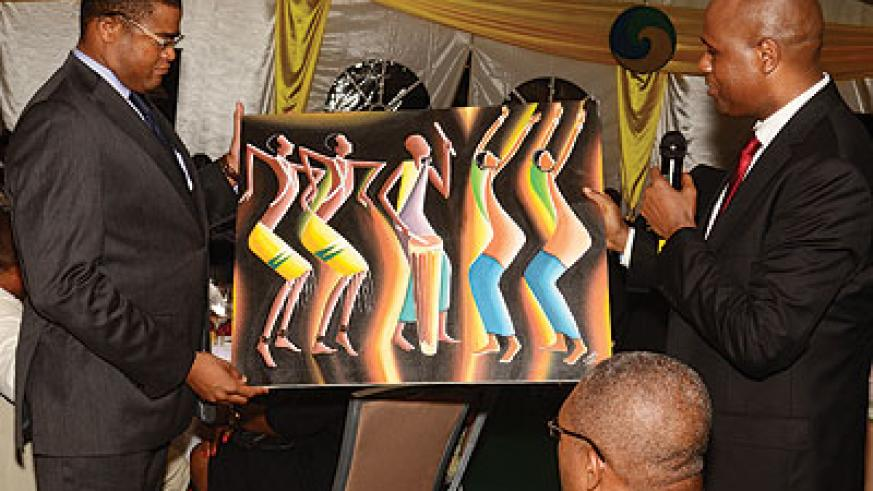 RwandAir boss John Mirenge (right), hands over a painting of a Rwandan cultural dance troupe to  Ludovic Ngwag (left), the secretary general of Littoral region in Cameroon, who rep....