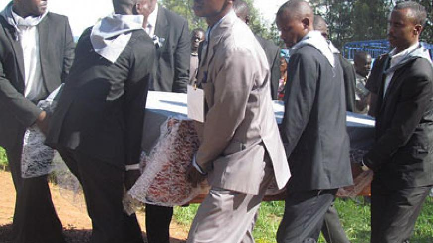 Mourners carry a coffin containing remains of a Genocide victim at Kinazi memorial site on Monday. JP Bucyensenge.