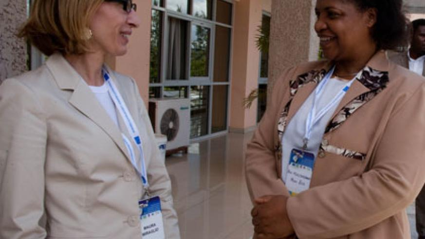 Miraglio (L) chats MP Mureshyankwano on the sideline of the symposium in Kigali yesterday. Timothy Kisambira.