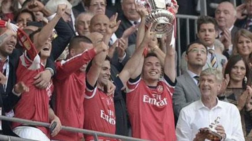 Arsenal's Thomas Vermaelen lifts the trophy as he celebrates with team mates after winning their FA Cup final against Hull. (Internet photo)