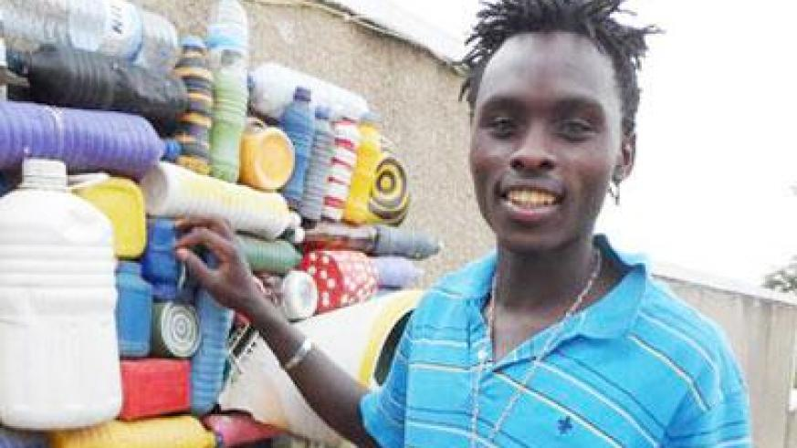 Timothy Wandulu poses by one of his pieces made from scrap. (Moses Opobo)