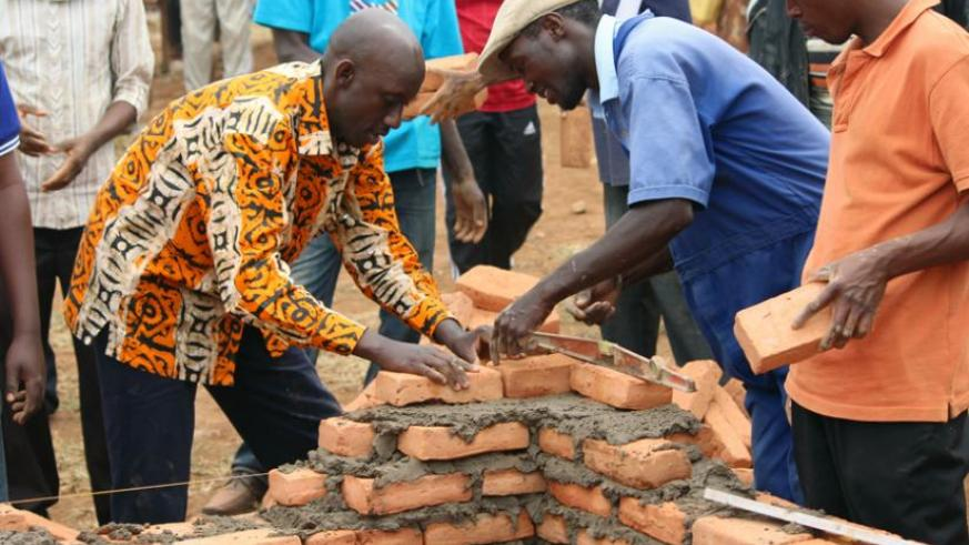 Minister Francis Kaboneka participates in Umuganda to build houses for Rwandans evicted from Tanzania at Jabana. (Clément Uwilingiyimana)