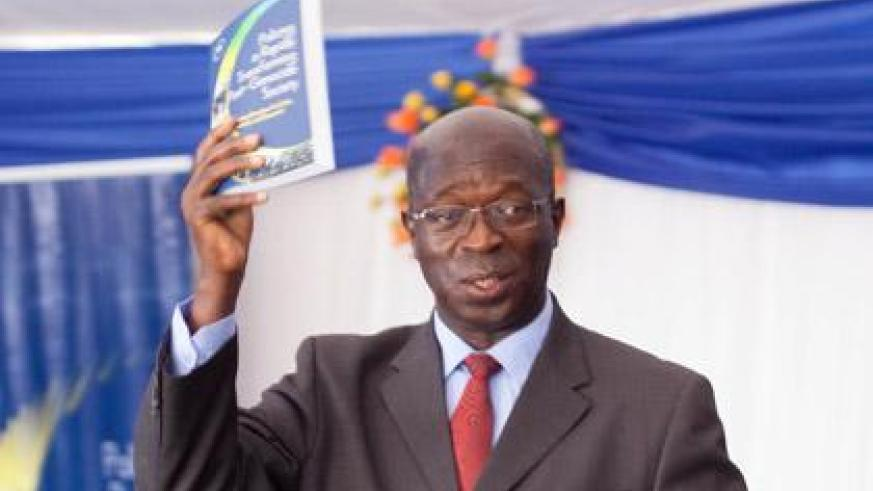 Prime Minister Anastase Murekezi lifting the Police Book after the launch. (Timothy Kisambira)